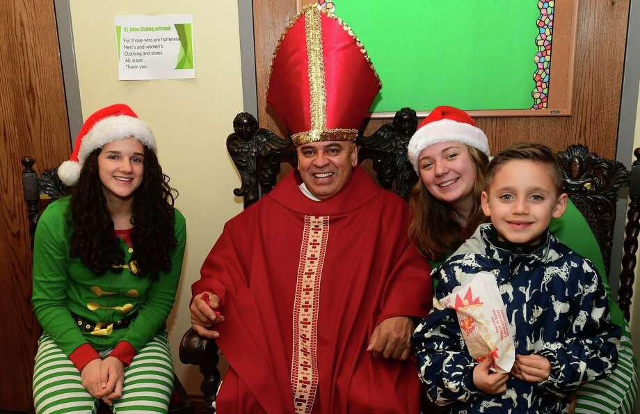 Danielle Gibson and Ava Maubert play elves to Hugo Carbajal's St. Nicholas for guest Nico Segovia, 9, as St. John's host their annual Christmas Village Saturday, December 14, 2019 at the church in Stamford, Conn. Actors and animals performed in a live nativity portraying various Christmas characters. For visitors there were lots of festive goodies including hot chocolate, cookies, popcorn and other treats. Photo: Erik Trautmann / Hearst Connecticut Media / Norwalk Hour