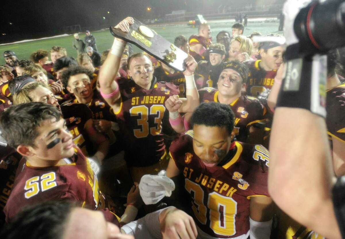 St Joseph celebrates their 17-13 win over Hand in the 2019 CIAC Class L state championship football game at Veterans Memorial Stadium in New Britian.