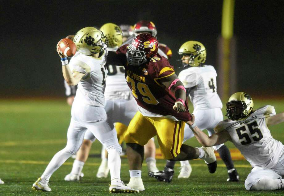 Hand quarterback Phoenix Billings hit on his pass by St. Joseph Jermaine Williams in the fourth quarter of the CIAC Class L state championship football game at Veterans Memorial Stadium in New Britian, Connecticut on Dec. 14, 2019. St. Joseph won 17-13. Photo: Matthew Brown / Hearst Connecticut Media / Stamford Advocate