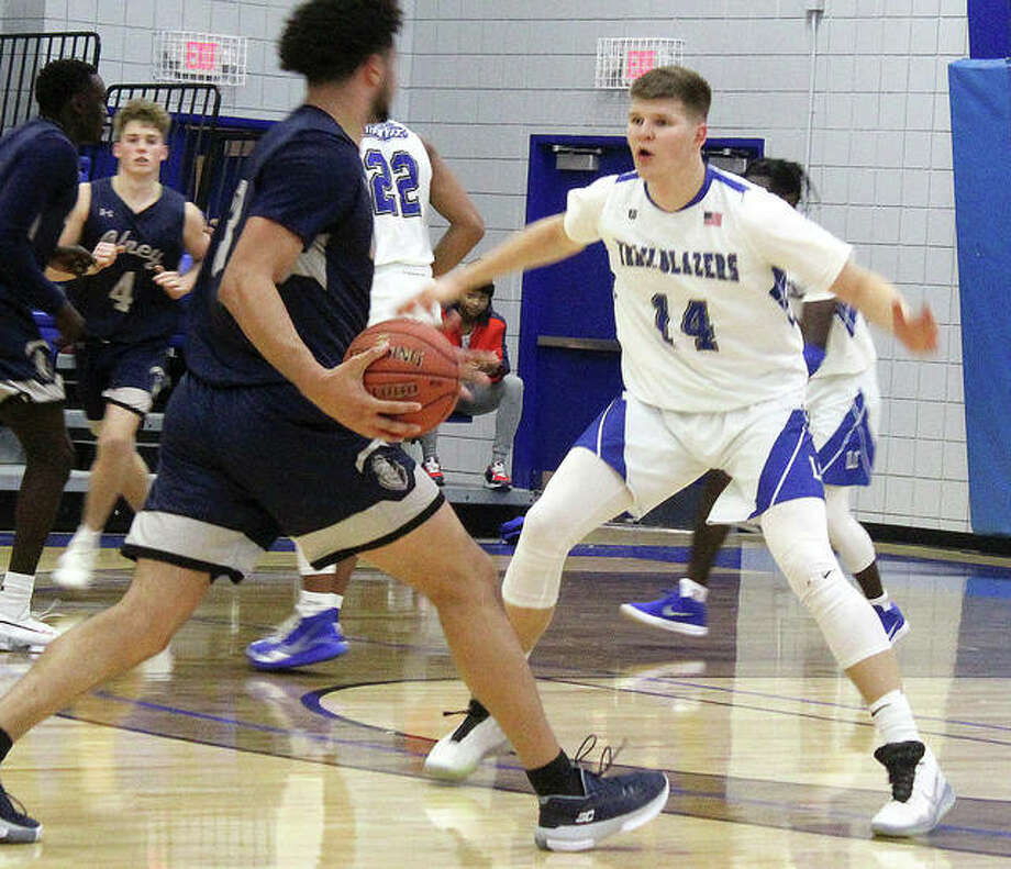 LCCC's Amandas Urkis (14) eyes Olney Central College's Elijah Farr in Saturday's District 16 game at the River Bend Arena. The Trailblazers upset to No. 14-ranked Blue knights 72-60. Photo: Pete Hayes | The Telegraph