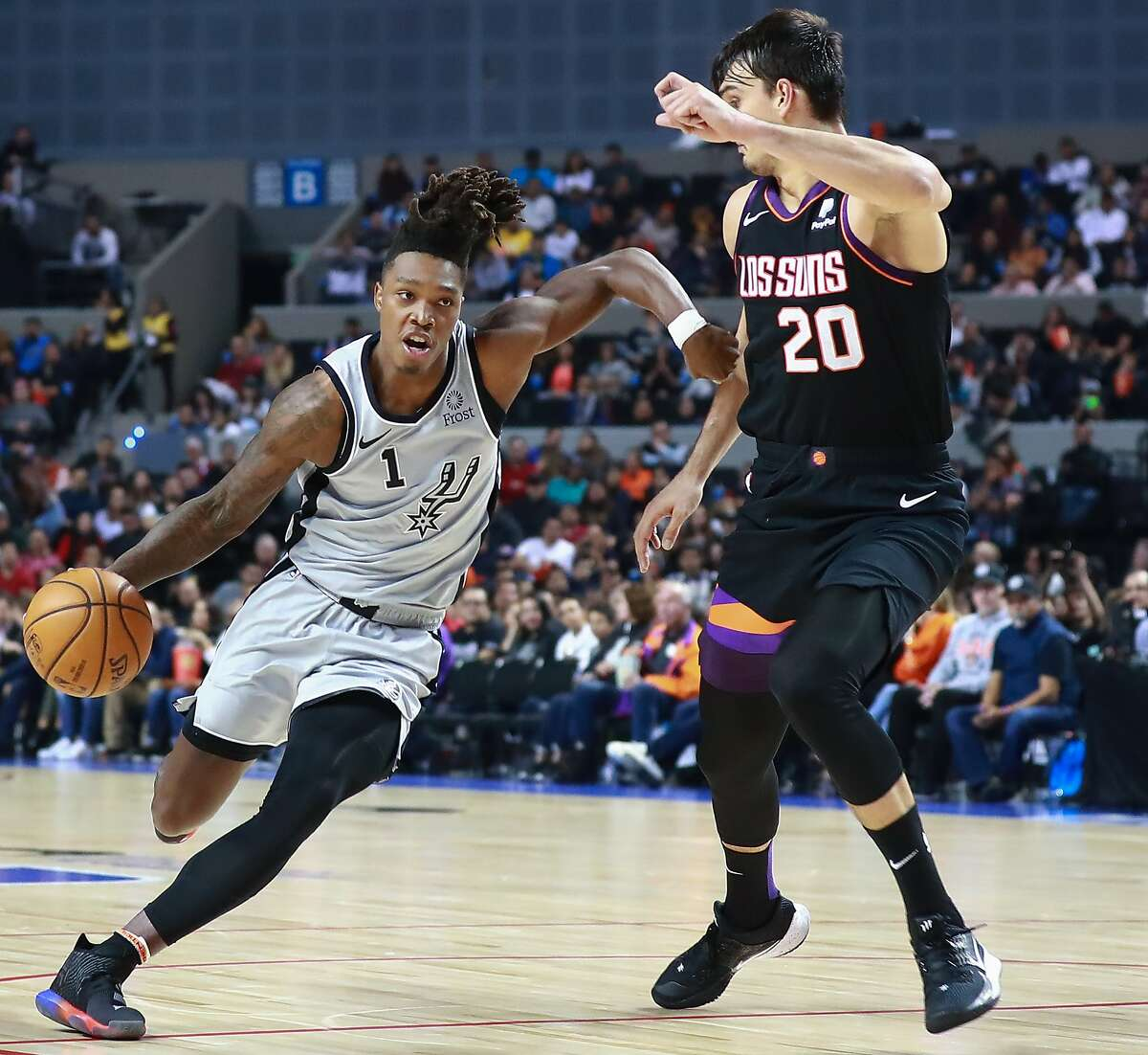 MEXICO CITY, MEXICO - DECEMBER 14: Lonnie Walker IV #1 of the San Antonio Spurs handles the ball against Dario Saric #20 of the Phoenix Suns during a game between San Antonio Spurs and Phoenix Suns at Arena Ciudad de Mexico on December 14, 2019 in Mexico City, Mexico. (Photo by Hector Vivas/Getty Images)