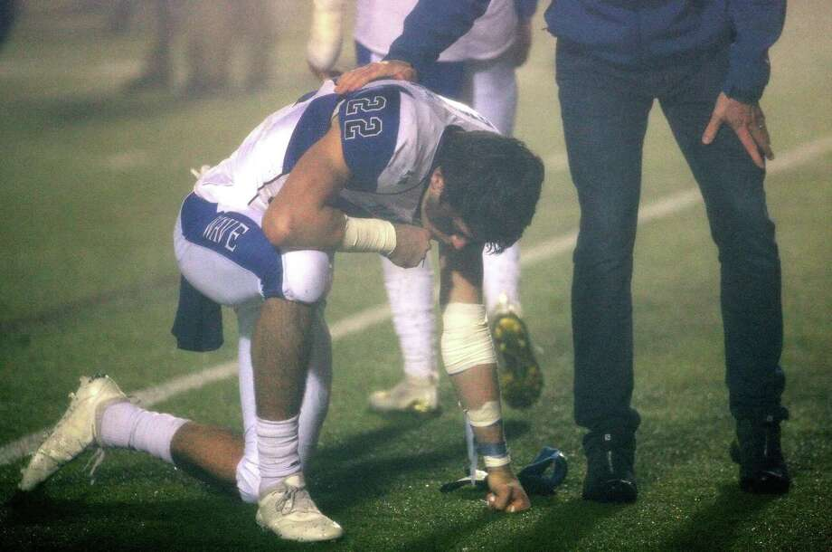 Darien's Jackson Peters kneels on the field after Darien fell to Newtown on Saturday. Photo: Christian Abraham / Hearst Connecticut Media / Connecticut Post