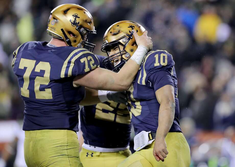 Navy's Malcolm Perry (10) gets a hug from teammate Ford Higgins after scoring a touchdown in the fourth quarter against Army. Photo: Elsa / Getty Images