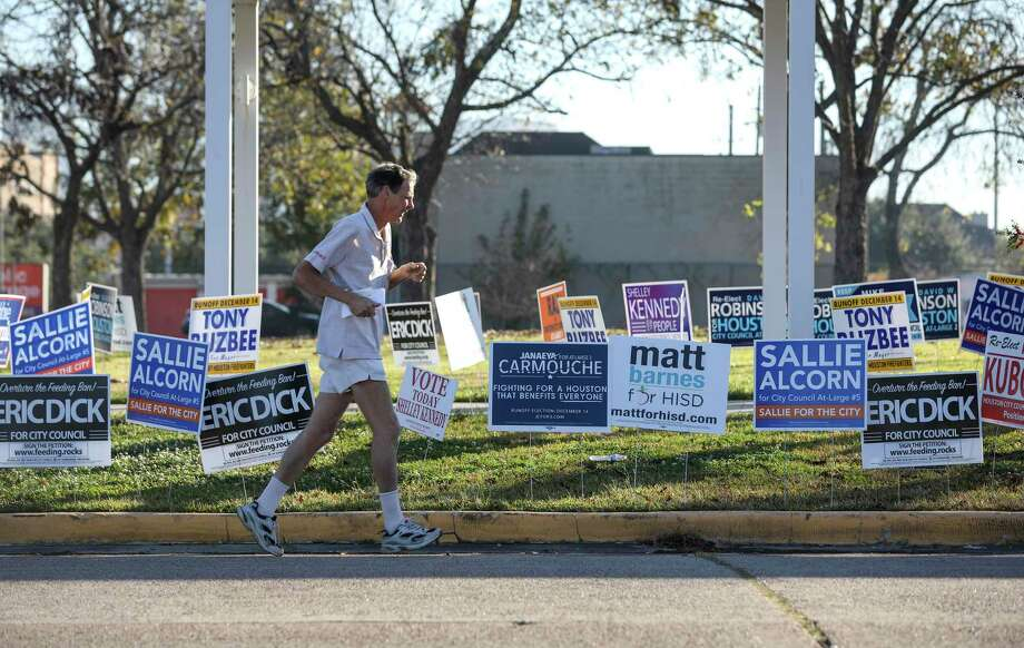 A man jogs by campaign signs on the last day of voting in a joint runoff election on Saturday, Dec. 14, 2019, in Houston. Photo: Jon Shapley, Houston Chronicle / Staff Photographer / © 2019 Houston Chronicle