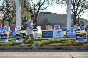 A man jogs by campaign signs on the last day of voting in a joint runoff election on Saturday, Dec. 14, 2019, in Houston.