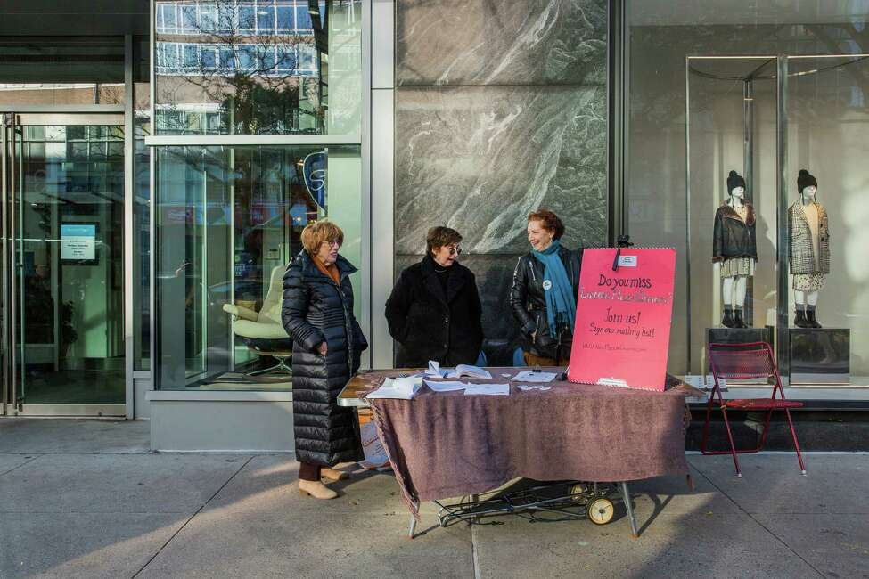 Volunteers, from left: Ruth Sussman; Norma Levy, New Plazaa€™s president; and Marjorie Borell man a table soliciting support for New Plaza Cinema, in Manhattan, Nov. 2, 2019. The grass-roots organization is comprised of fans of the now shuttered Lincoln Plaza Cinemas art house theater. The group currently screens movies twice monthly at a rented auditorium, and is looking for a way to establish a new, permanent cinema home. (Sarah Stacke/The New York Times)