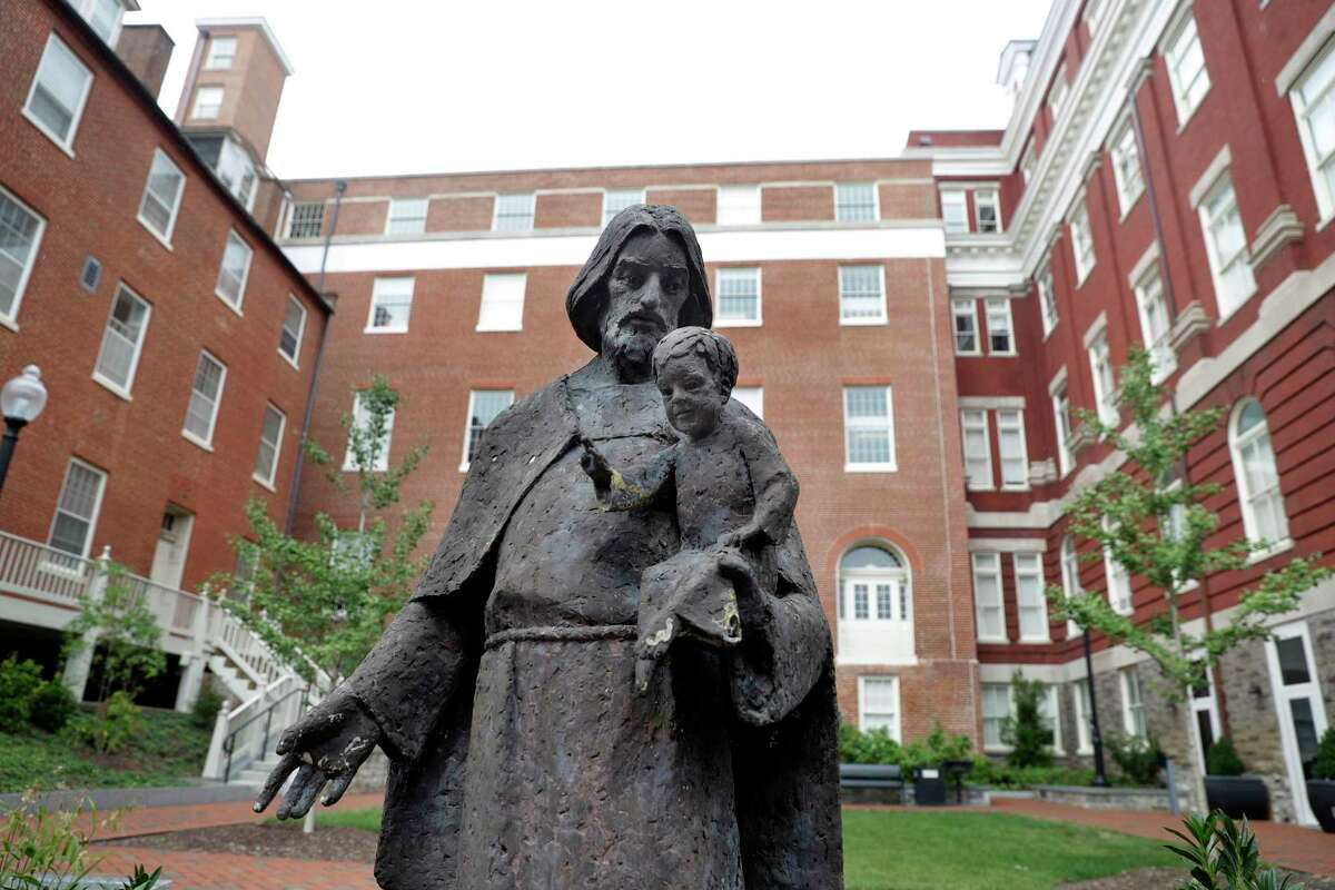 FILE- In this Sept. 1, 2016 file photo, a Jesuit statue is seen in front of Freedom Hall, formerly named Mulledy Hall, on the Georgetown University campus in Washington. Georgetown University and two theological seminaries have announced plans for reparations to benefit descendants of the enslaved people who played a role in the institutions' success. At least 56 universities have joined a University of Virginia-led consortium, Universities Studying Slavery, to explore their ties to slavery and share research and strategies. (AP Photo/Jacquelyn Martin, File)