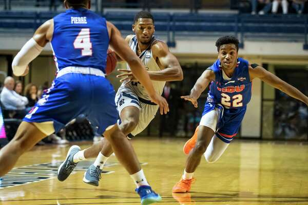 Rice guard Chris Mullins (24) dribbles past Houston Baptist guard Jason Gates (22) and Myles Pierre (4) in the first half of a college basketball game Saturday, Dec 14, 2019, in Houston.