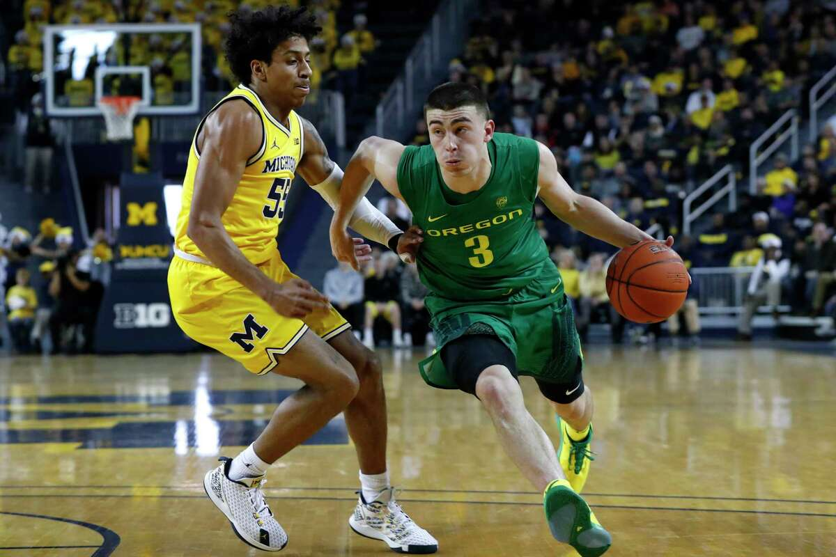 Oregon guard Payton Pritchard (3) drives on Michigan guard Eli Brooks (55) during the first half of an NCAA college basketball game in Ann Arbor, Mich., Saturday, Dec. 14, 2019. (AP Photo/Paul Sancya)