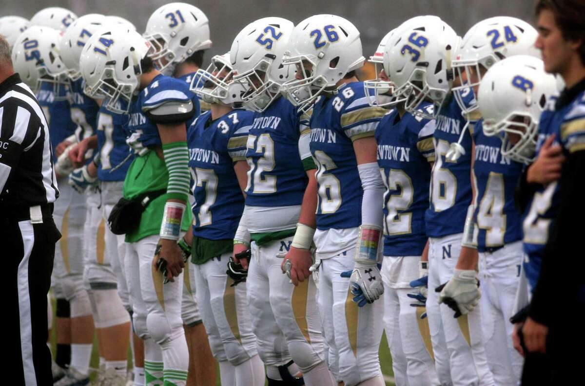 Newtown players hold hands during a moment of silence on the 7th of the Sandy Hook school shooting before the start of CIAC Class LL Championship football action against Darien in Trumbull, Conn., on Saturday Dec. 14, 2019.