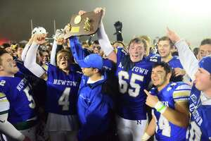 The Newtown football team celebrates its 13-7 win over Darien in the Class LL football championship on Saturday in Trumbull.