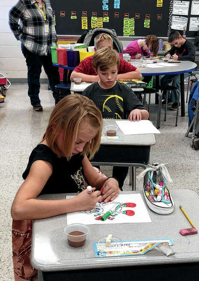"""Jaici Yanczer (front), a student in Mrs. Evans' class at Pleasant Hill Elementary School, colors her """"Fred the Dancing Soybean"""" Christmas coloring page during a recent visit by the Pike-Scott Agriculture in the Classroom program. Students learned how soybeans are grown; what types of products contain soybeans, including soy candles and soy sauce; and got to taste two soybean products, chocolate soy milk and tofu. Students also watched videos on the production of soy milk and tofu and one on how soybeans are grown and shipped around the world Photo: Photo Provided"""