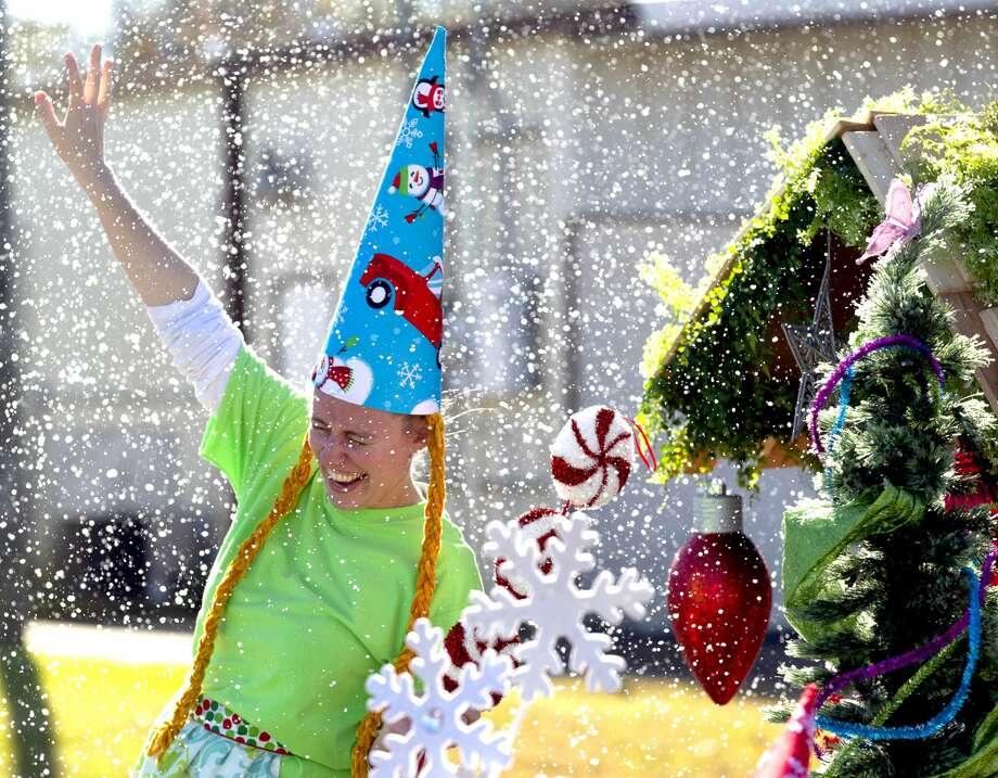Chrissa Silva with Carolina Creek Christian Camp enjoys fake snow during the annual Christmas parade through downtown Conroe, Saturday, Dec. 14, 2019. Photo: Jason Fochtman/Staff Photographer