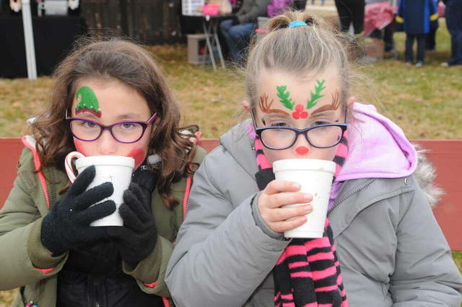 Stella Egelhoff, 8, of Grafton and Anjalee Fanning, 9, of Hardin, savor hot chocolate served during Christmas in Calhoun on Saturday in Hardin.