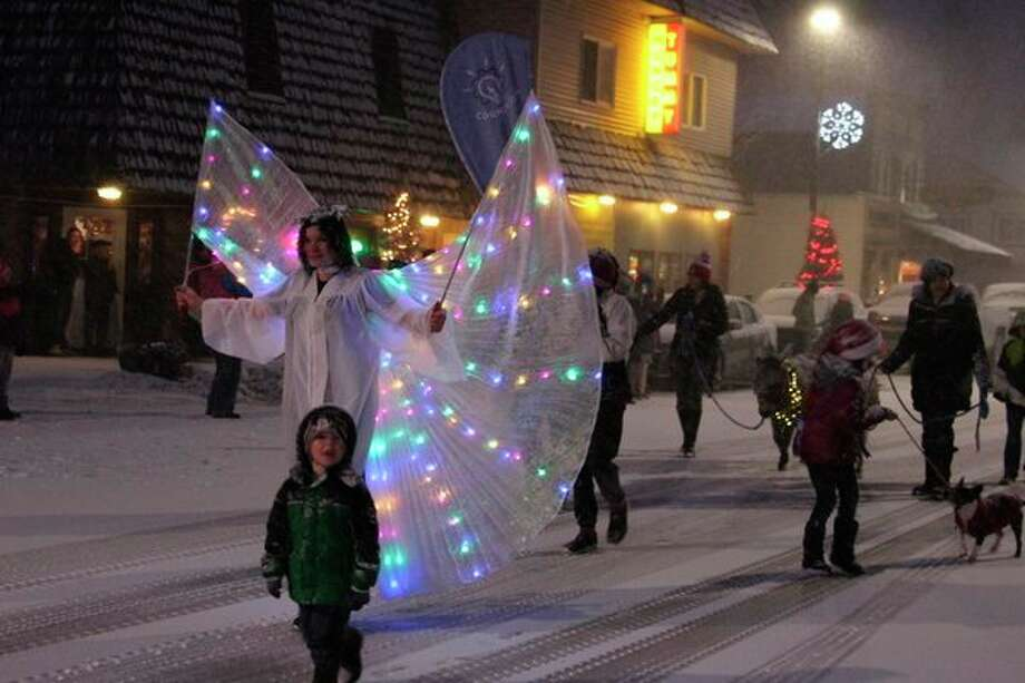 An angel lights the way for the rest of the Cognition entry to the Christmas Magic Parade, which included several donkeys. (Photo/Colin Merry)