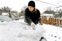 Nick Boss brushes the snow off of his car at his home on Dewey Avenue in Edwardsville back in November during the first major snowfall of the season.