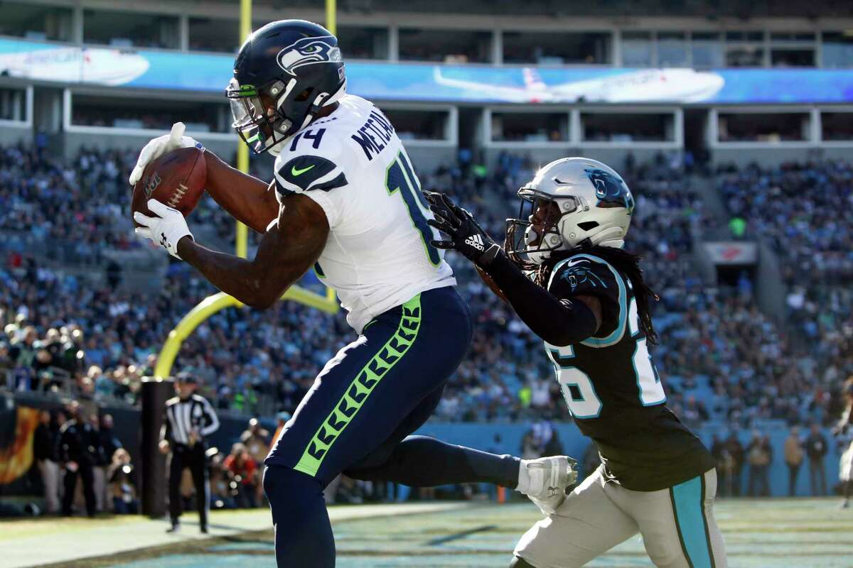 Seattle Seahawks wide receiver D.K. Metcalf (14) catches a touchdown pass as Carolina Panthers cornerback Donte Jackson chases during the first half of an NFL football game in Charlotte, N.C., Sunday, Dec. 15, 2019.
