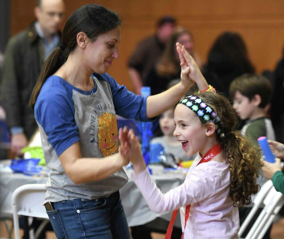 Greenwich's Emma Levine, 7, dances with her mother, Becca Levine, at the Donuts, Dreidels & DJ Chanukah Party at Temple Sholom in Greenwich, Conn. Sunday, Dec. 15, 2019. The celebration featured music and games on the dance floor by DJ Adam Craig as well as arts and crafts, a holiday boutique, book fair, and latkes, donuts and lunch. Photo: Tyler Sizemore / Hearst Connecticut Media / Greenwich Time