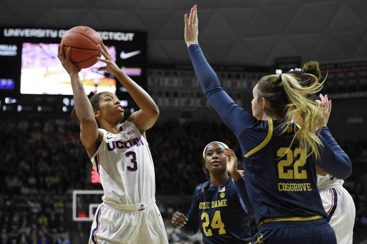 UConn's Megan Walker, left, is guarded by Notre Dame's Destinee Walker, center, and Danielle Cosgrove, right, in the first half in December.
