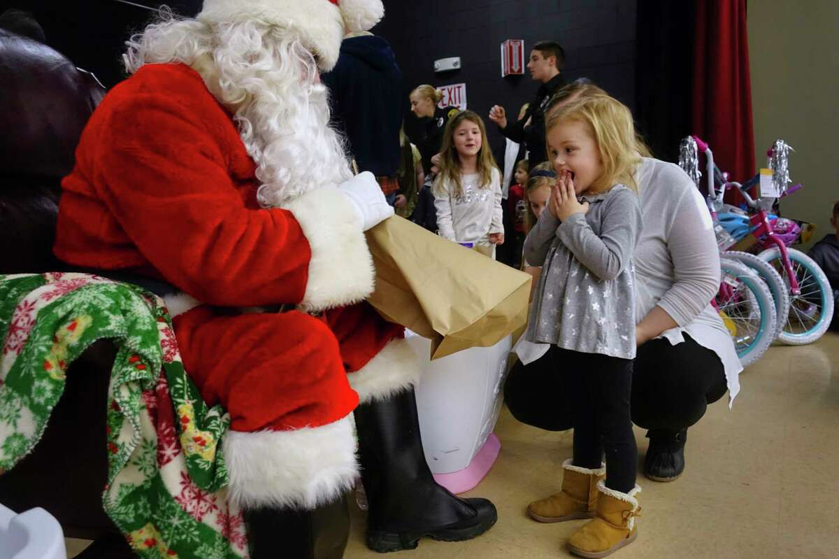 Cailey McEwan, 2, of Selkirk is excited to see Santa at the Albany County Sheriff Hilltown Christmas event on Sunday, Dec. 15, 2019, in New Scotland, N.Y. The event, which began 31 years ago, is held to help parents in the rural areas of Albany County to provide Christmas gifts for their children. Sheriff Craig Apple said that 31 years ago it started with a single family and that Sunday's event would host 300 people. A large percentage of the volunteer work done for the event, and the purchasing of the toys and clothing, is done by Sheriff department employees and their family members. (Paul Buckowski/Times Union)
