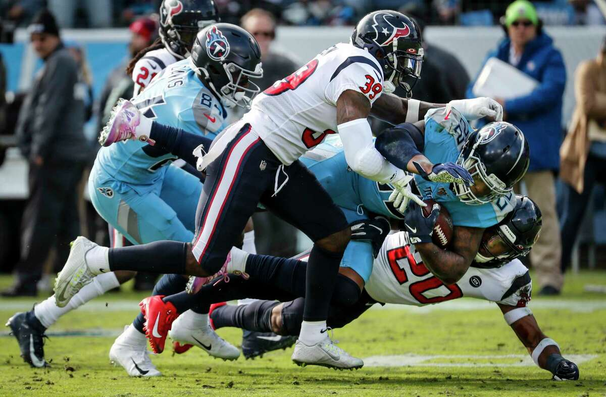 Tennessee Titans running back Derrick Henry (22) is stopped by Houston Texans free safety Tashaun Gipson (39) and strong safety Justin Reid (20) during the second quarter of an NFL football game at Nissan Stadium on Sunday, Dec. 15, 2019, in Nashville.