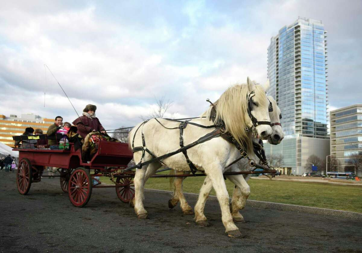 A horse-drawn carriage rides through Mill River Park in Stamford, Conn. Sunday, Dec. 15, 2019. Horse-drawn carriage rides were given at Mill River Park on Sunday, along with skating at the Steven and Alexandra Cohen Skating Center and beer tasting at the Half Full Winter Beer Garden.