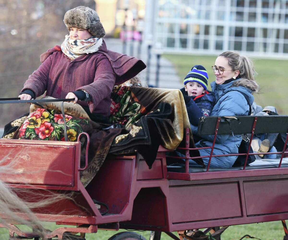 Stamford's Camila Gustavo and her son Antonio, 5, ride on a horse-drawn carriage through Mill River Park.