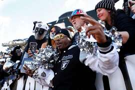 Oakland Raiders' fan MC Hammer poses with Black Hole members before Raiders' final game at Oakland Coliseum in Oakland, Calif., on Sunday, December 15, 2019.