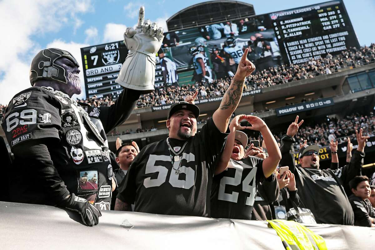 From left: Oakland Raiders fans Sharrieff Saalakhan, Shine Nieto and his son Craig Nieto, 10, during the first half of an NFL game against the Jacksonville Jaguars at the Oakland-Alameda County Coliseum on Sunday, Dec. 15, 2019, in Oakland, Calif.