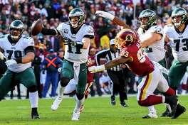 Philadelphia Eagles quarterback Carson Wentz runs out of the pocket as Washington Redskins defensive end Jonathan Allen closes in at FedEx Field on Sunday, Dec. 15, 2019.