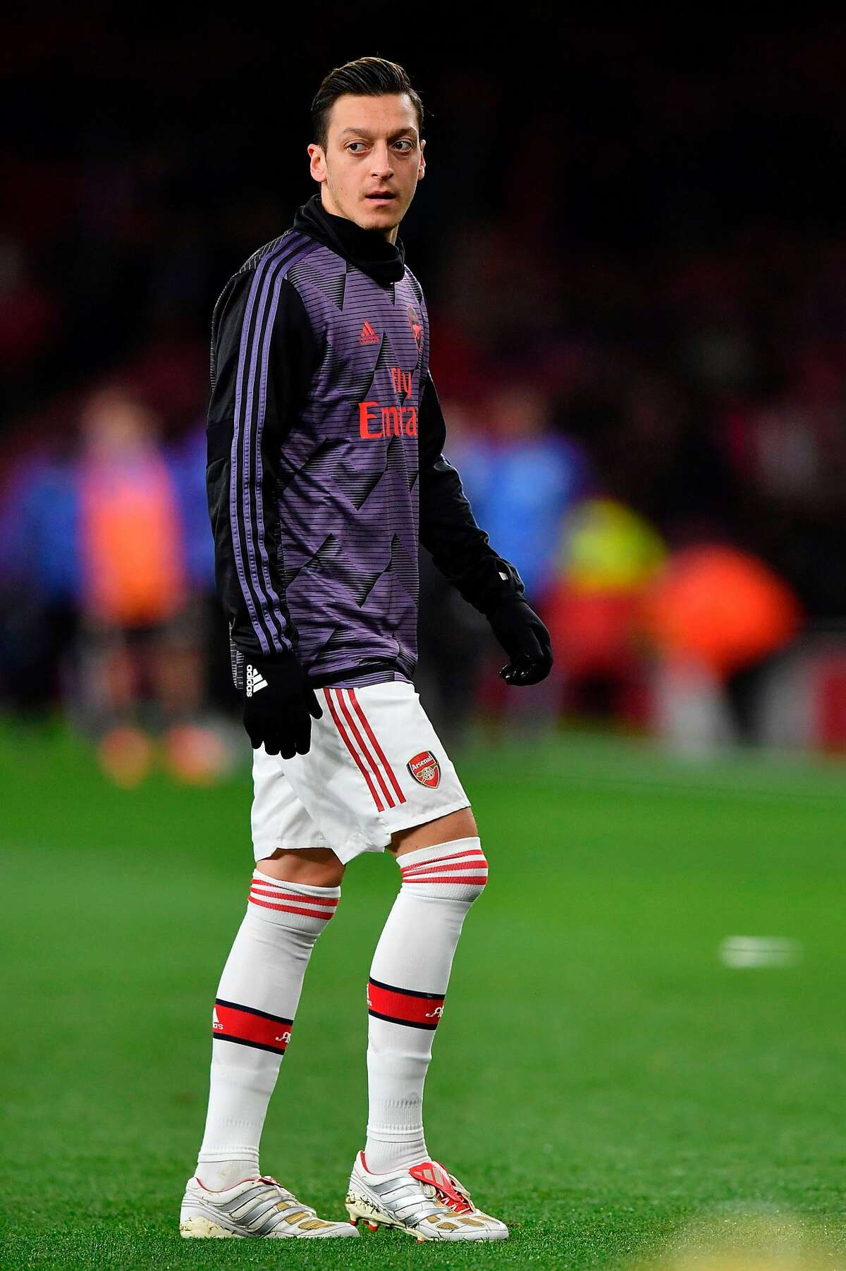 Arsenal's German midfielder Mesut Ozil warms up for the English Premier League football match between Arsenal and Manchester City at the Emirates Stadium in London on December 15, 2019. (Photo by Ben STANSALL / AFP) / RESTRICTED TO EDITORIAL USE. No use with unauthorized audio, video, data, fixture lists, club/league logos or 'live' services. Online in-match use limited to 120 images. An additional 40 images may be used in extra time. No video emulation. Social media in-match use limited to 120 images. An additional 40 images may be used in extra time. No use in betting publications, games or single club/league/player publications. / (Photo by BEN STANSALL/AFP via Getty Images)