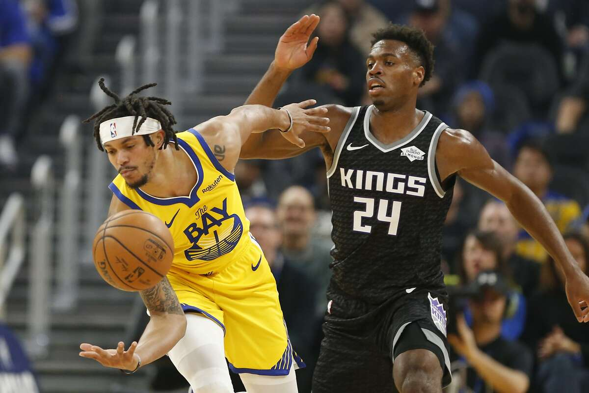 Sacramento Kings guard Buddy Hield (24) battles for the ball against Golden State Warriors gurad Damion Lee (1) during the first half of an NBA basketball game in San Francisco, Sunday, Dec. 15, 2019. (AP Photo/Jed Jacobsohn)