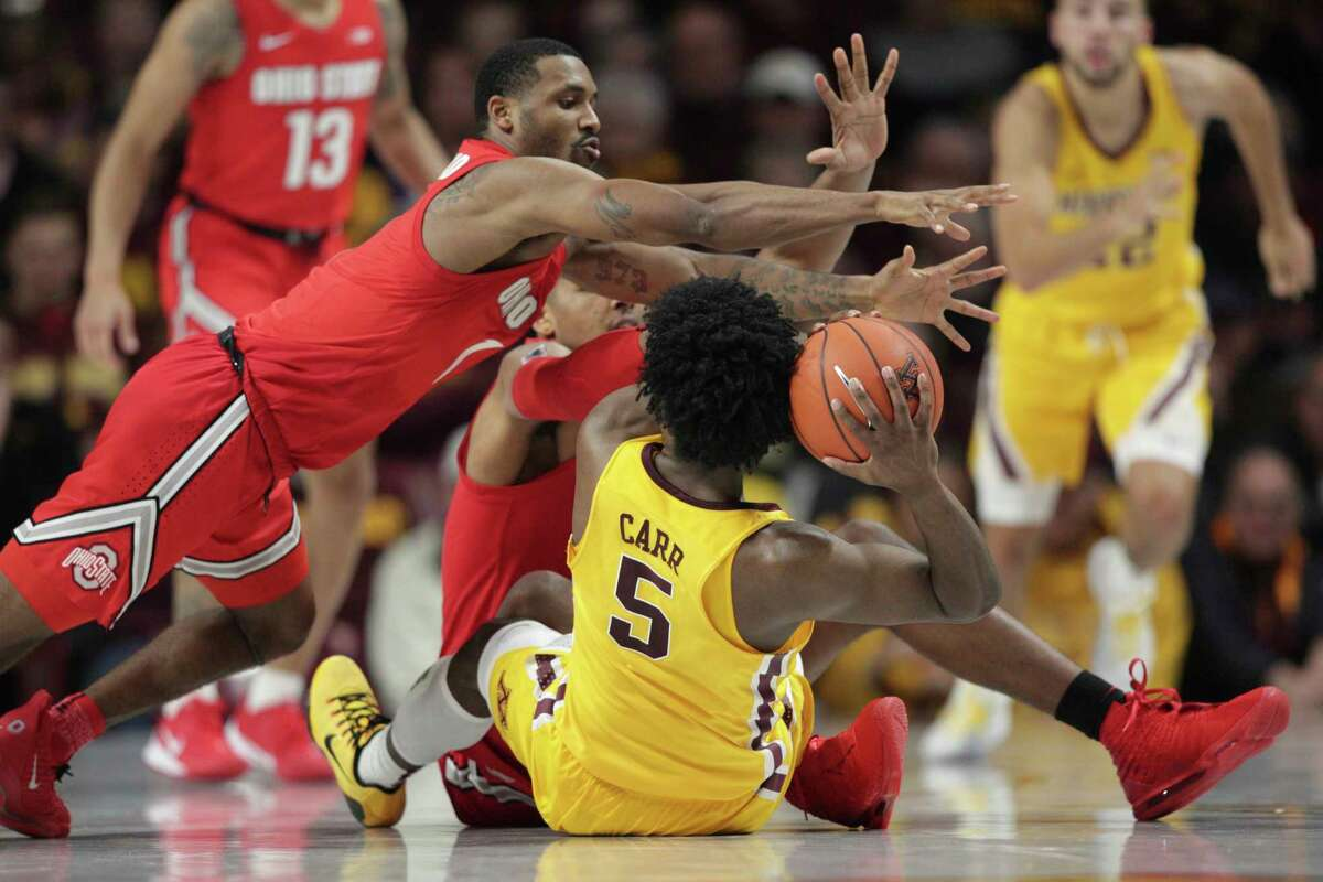 Minnesota guard Marcus Carr (5) looks to pass as Ohio State guard Luther Muhammad (1) and forward Andre Wesson (24) dive in during the second half in an NCAA college basketball game Sunday, Dec. 15, 2019, in Minneapolis. (AP Photo/Andy Clayton-King)