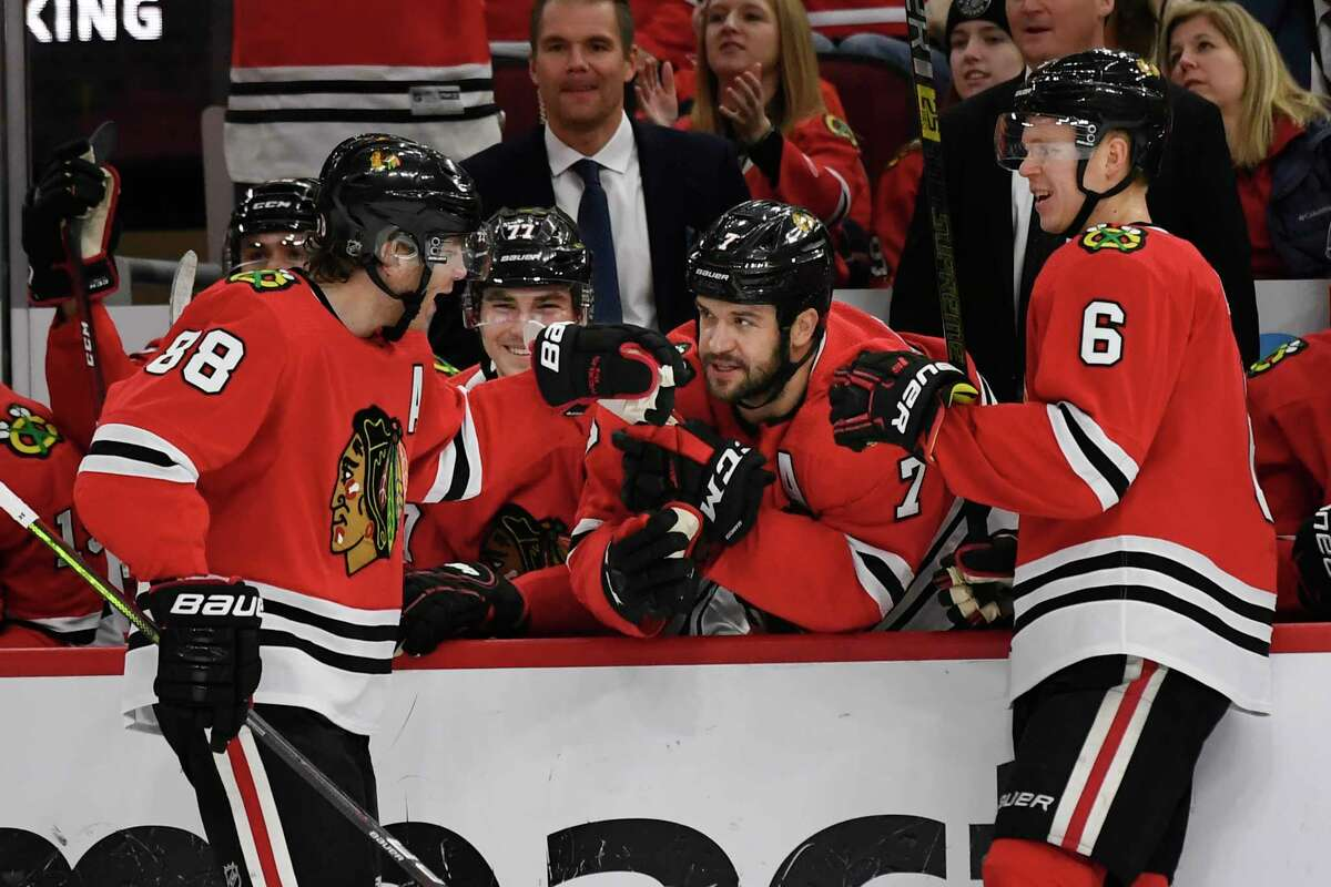Chicago Blackhawks' Patrick Kane (88) celebrates with teammate Brent Seabrook (7) on the bench after scoring a goal during the first period of an NHL hockey game against the Minnesota Wild, Sunday, Dec. 15, 2019, in Chicago. (AP Photo/Paul Beaty)
