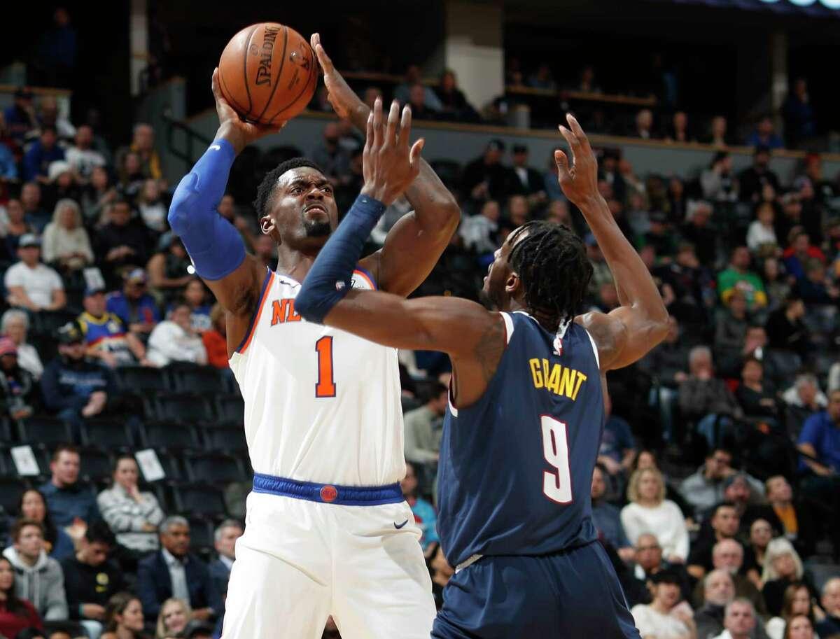 New York Knicks forward Bobby Portis, left, shoots for a basket over Denver Nuggets forward Jerami Grant in the first half of an NBA basketball game Sunday, Dec. 15, 2019, in Denver. (AP Photo/David Zalubowski)