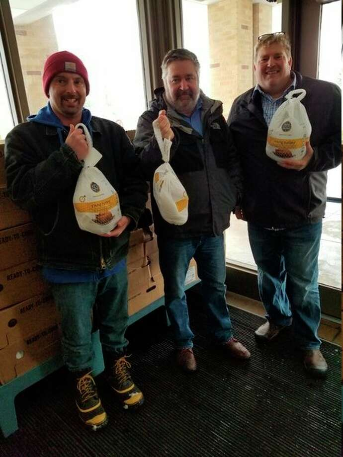 Mike Cnudde (center), of Coldwell Banker A.L.M. Realty & Associates, Inc., donated 100 turkeys to theMatthew 25:35 Food Pantry in November. (Courtesy photo)