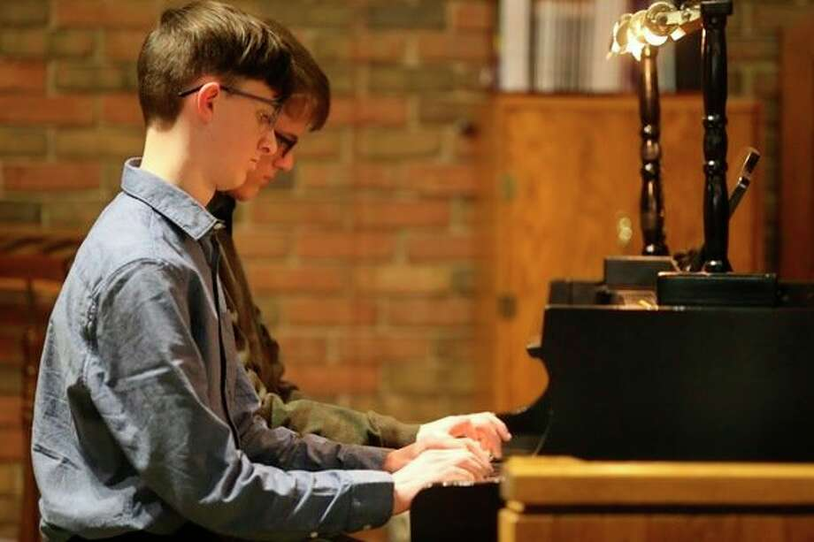 "Owen and Aidan Forrester, of Ludington, perform a ""Spider-Man"" duet during a piano recital at Manistee United Methodist Church for Melinda Lise Pokorzyski's students. (Courtesy photo/Andy Klevorn)"