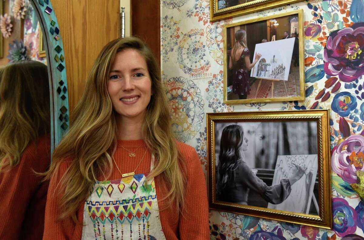 Gretchen Tisch, a local artist who paints live during a wedding for the couple, is seen next to photos of her at weddings in her studio on Friday, Oct. 25, 2019 in Saratoga Springs, N.Y. (Lori Van Buren/Times Union)