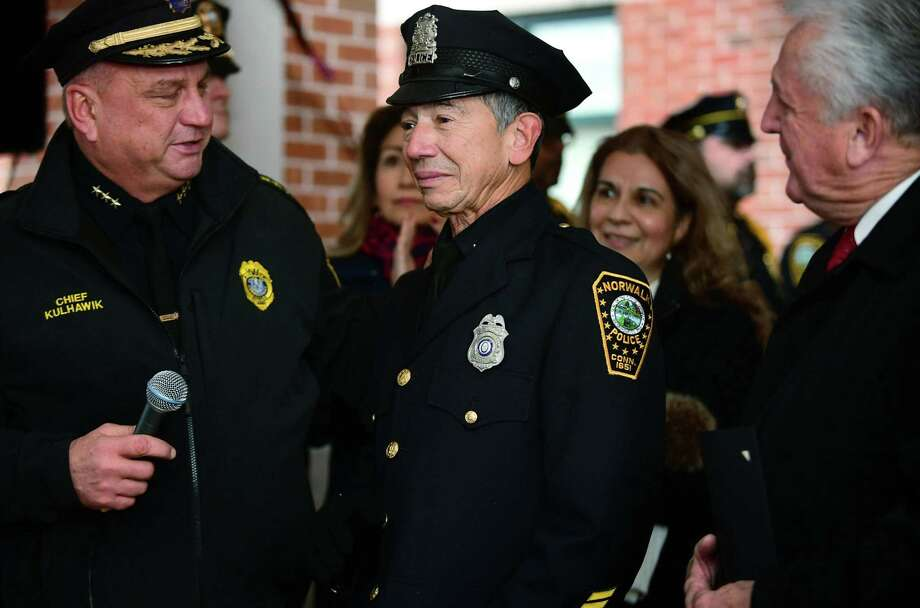 Police officers city officials and local residents greet Officer Cesar Ramirez, a 32-year member of the force, as he is given a sendoff Friday, December 13, 2019, at Norwalk Police Headquarters in Norwalk, Conn. Ramirez was recently diagnosed with brain cancer and is retiring. Photo: Erik Trautmann / Hearst Connecticut Media / Norwalk Hour