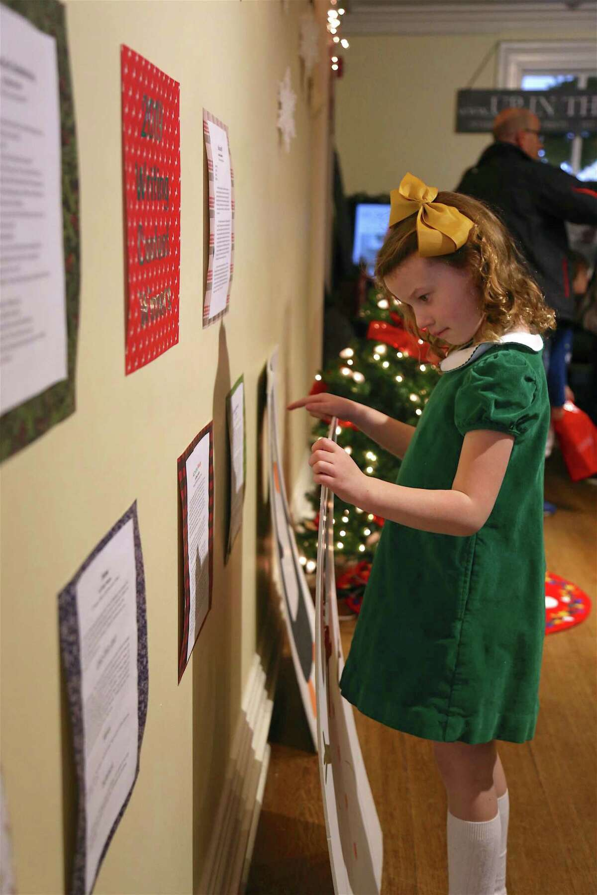 Henriette Greiner, 6, of Fairfield, reads some writing contest entries at the annual Visit to Santa's House at Burr Homestead on Sunday, Dec. 15, 2019, in Fairfield, Conn.