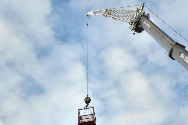 Workers access a cell tower with a crane along Connecticut Avenue in Norwalk, Conn., Dec. 15, 2016.
