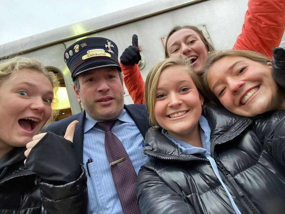 The Depot's Anne-Lise Finn, Claire Hannigan, Anna Corney, and Kate Bellissimo with a Metro-North train conductor on Friday, when The Depot was handing out free breakfast sandwiches. Photo: The Depot