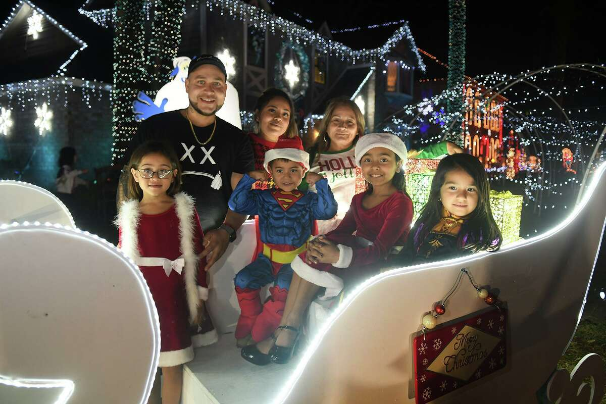 Carlos and Ashley Perez, top from left, along with grandma Bertha Bonilla, and children Jayleen Perez, 7, front from left, Carlos Perez Jr., 4, Jaycee Perez, 10, amd Toni Bonilla, 6, pose for a family photo in a sleigh in front of their home at 8130 Dorrcrest in Prestonwood Forest before the opening of judging on Dec. 14, 2019.