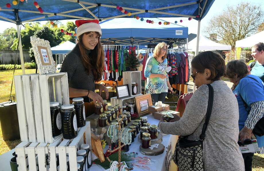 Lauren Inmon, left, of Huntsville, serves her customers at her Honey Llama booth during the Holiday in the Gardens at Mercer Botanic Gardens in Humble on Saturday. Photo: Jerry Baker, Houston Chronicle / Contributor / Houston Chronicle