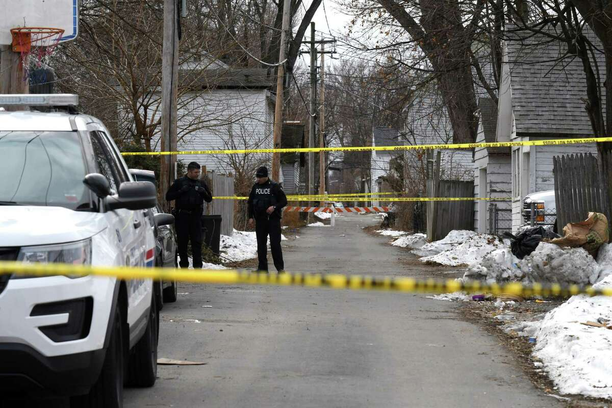 Troy Police investigate the scene in an ally behind a Fifth Avenue home between 119th and 120th streets where a woman was shot dead and a man tried to kill himself on Monday, Dec. 16, 2019, in Troy, N.Y. (Will Waldron/Times Union)