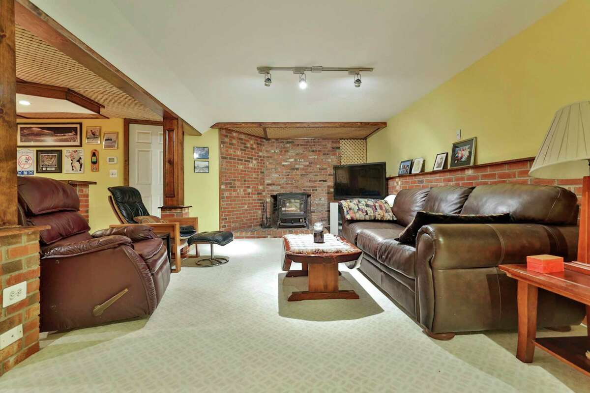 One the partially finished lower level there is a sitting or media room with a wood stove against a red brick wall.