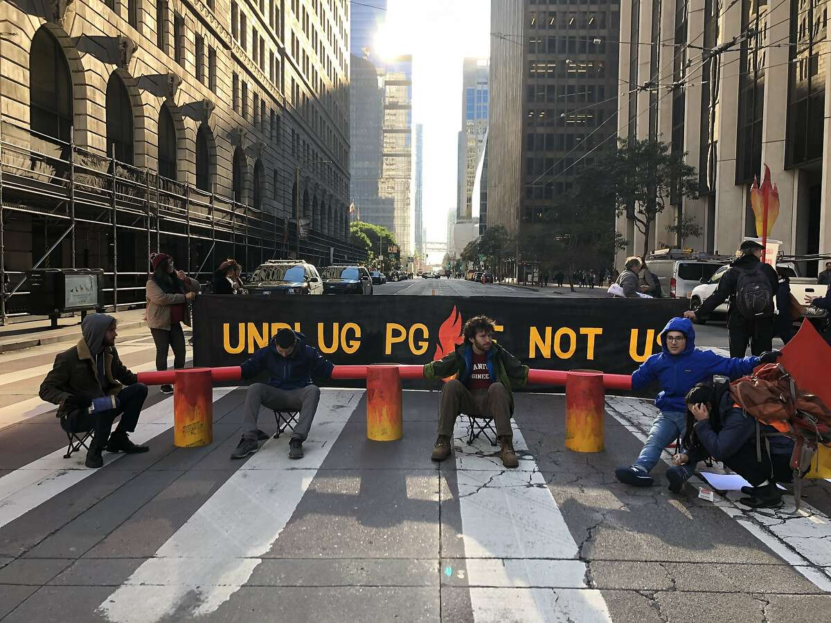 People protesting against PG&E chained themselves together to block the intersection of Beale and Mission streets Monday, December 16, 2019.
