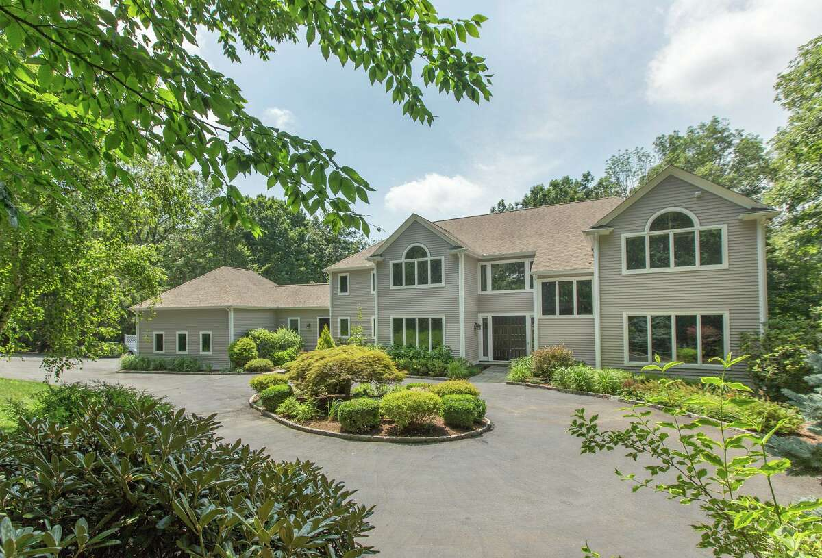 The taupe-colored custom-built contemporary colonial house at 15 Partridge Lane features 14 rooms and 6,088 square feet of living space.