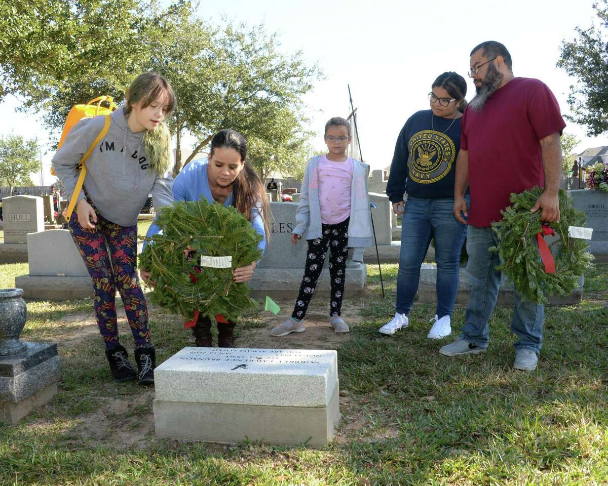 Crystal Prezas and daughter Cabbryn (10) place a wreath on a grave with assistance of Sofia (8), Hailee (14) and Erick Rodriguez during the National Wreaths Across America Ceremony at Magnolia Cemetery, Saturday, December 14, 2019 in Katy, TX.
