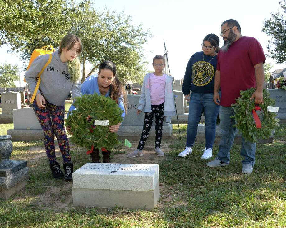 Crystal Prezas and daughter Cabbryn (10) place a wreath on a grave with assistance of Sofia (8), Hailee (14) and Erick Rodriguez during the National Wreaths Across America Ceremony at Magnolia Cemetery, Saturday, December 14, 2019 in Katy, TX. Photo: Craig Moseley, Houston Chronicle / Staff Photographer / ©2019 Houston Chronicle